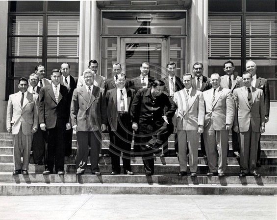 Comedian Jackie Gleason posing with a group of men at Buick Plant
